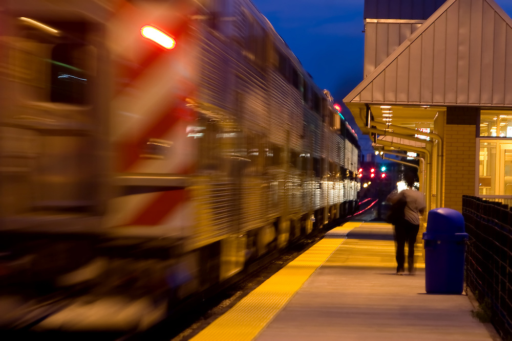 A single commuter has detrained at the Grand/Cicero station in Chicago as the Metra train pulls away, headed for the suburbs.