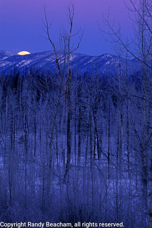 Full moon setting over the Whitefish Range from Polebridge. North Fork Flathead Valley, Montana