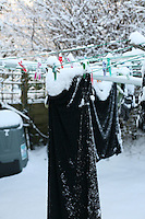 Black dress covered in snow on clothes line in Dublin Ireland November 2010