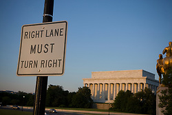 """A sign that reads """"Right Lane MUST Turn Right"""" on the Arlington Memorial Bridge in front of the Lincoln Memorial in Washington, DC...The Lincoln Memorial is located on the National Mall in Washington, D.C. It is a United States Presidential memorial built to honor the 16th president of the United States, Abraham Lincoln. The architect was Henry Bacon, the sculptor was Daniel Chester French, and the painter of the interior murals was Jules Guerin...The building is in the form of a Greek Doric temple and contains a large seated sculpture of Abraham Lincoln and inscriptions of two well-known speeches by Lincoln. The memorial has been the site of many famous speeches, including Martin Luther King's """"I Have a Dream"""" speech, delivered on August 28, 1963, during the rally at the end of the March on Washington for Jobs and Freedom...Like other monuments on the National Mall, including the nearby Vietnam Veterans Memorial, Korean War Veterans Memorial, and National World War II Memorial, the Lincoln Memorial is administered by the National Park Service under its National Mall and Memorial Parks group. The National Memorial has been listed on the National Register of Historic Places since October 15, 1966. It is open to the public 24 hours a day. In 2007, it was ranked seventh on the List of America's Favorite Architecture by the American Institute of Architects."""