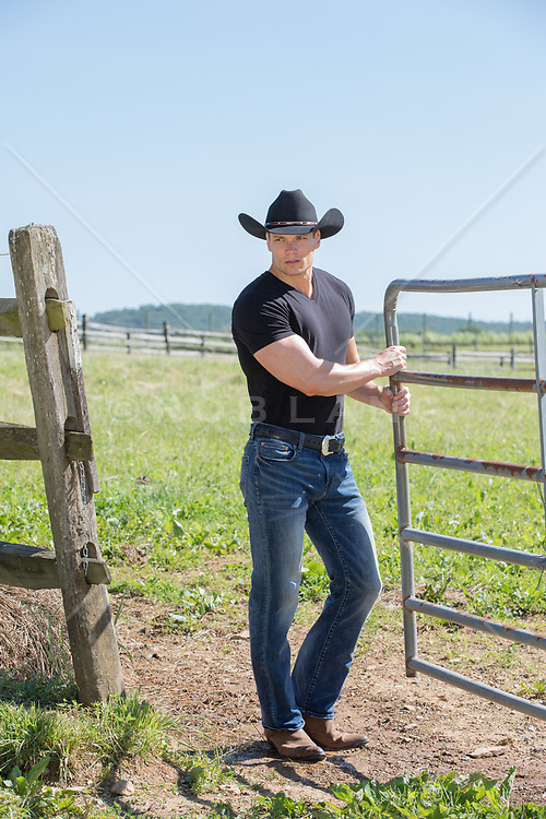hot cowboy with open shirt holding a saddle cowboy opening a gate on a ranch