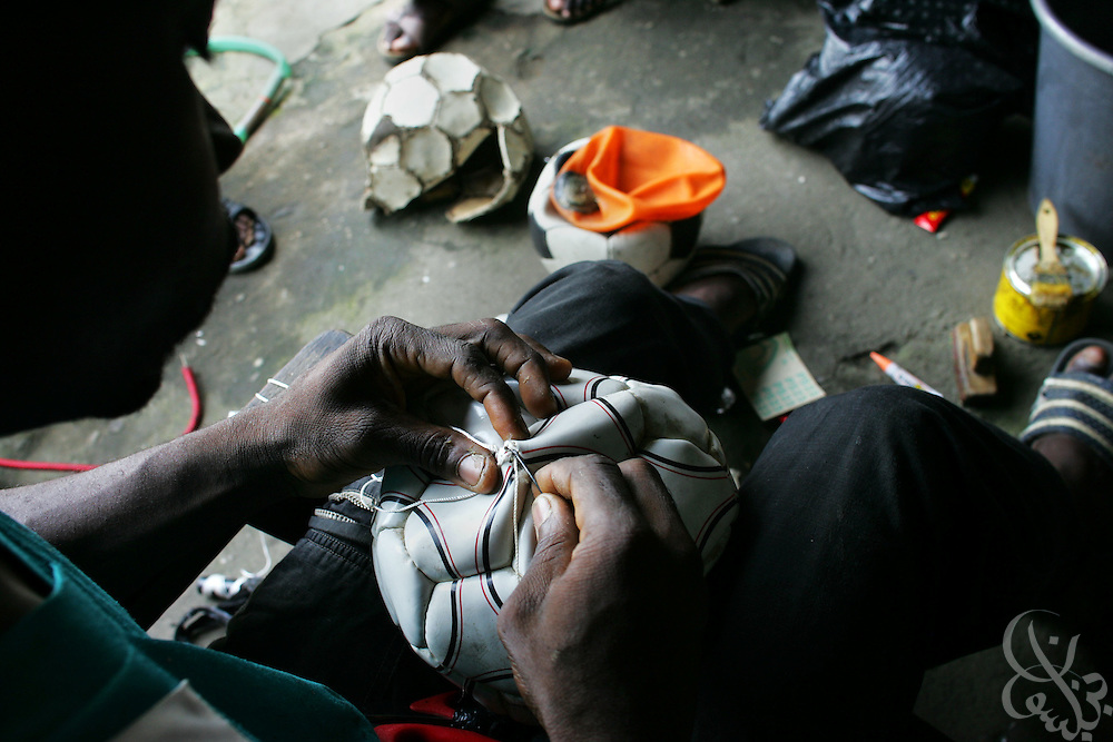 "Blaise N'cho, age 29, patches a football in the Abobo neighborhood of Abidjan, Côte d'Ivoire February 19,2006.  N'Cho, a shoe repairman, who's skill at repairing balls has earned him the reverent nickname  ""Le Seigneur"", or ""the Lord"", charges $1 per ball for most repairs and works out of his small family home."
