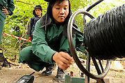 "Female Deputy Team Leader, Phisamai Linsaiyoum, age 20, prepares the last steps connecting the firing device to the black firing wire.  She admitted, ""Just after the large explosion I am very happy because if there is a misfire then I have to go and inspect what is wrong.  At that time it is very dangerous.  But so far I never have a misfire.""..She detonated 76, BLU 26 cluster bombs, laying buried in the dirt after being located by one of the Mines Advisory Group ladies teams.  She disposed of the bombs without moving them in a controled demolition using TNT and C4 explosives.  It took the team 7 days to clear 14,352 sq meters...Laos was part of a ""Secret War"", waged within its borders primarily by the USA and North Vietnam.  Many left over weapons supplied by China and Russia continue to kill.  However, between 90 and 270 million fist size cluster bombs were dropped on Laos by the USA, with a failure rate up to 30%.  Millions of live cluster bombs still contaminate large areas of Laos causing death and injury.  The US Military dropped approximately 2 million tons of bombs on Laos making it, per capita, the most heavily bombed country in the world. ..The women of Mines Advisory Group (MAG) work everyday under dangerous conditions removing unexploded ordinance (UXO) from fields and villages...***All photographs of MAG's work must include (either on the photo or right next to it) the credit as follows:  Mine clearance by MAG (Reg. charity)***."