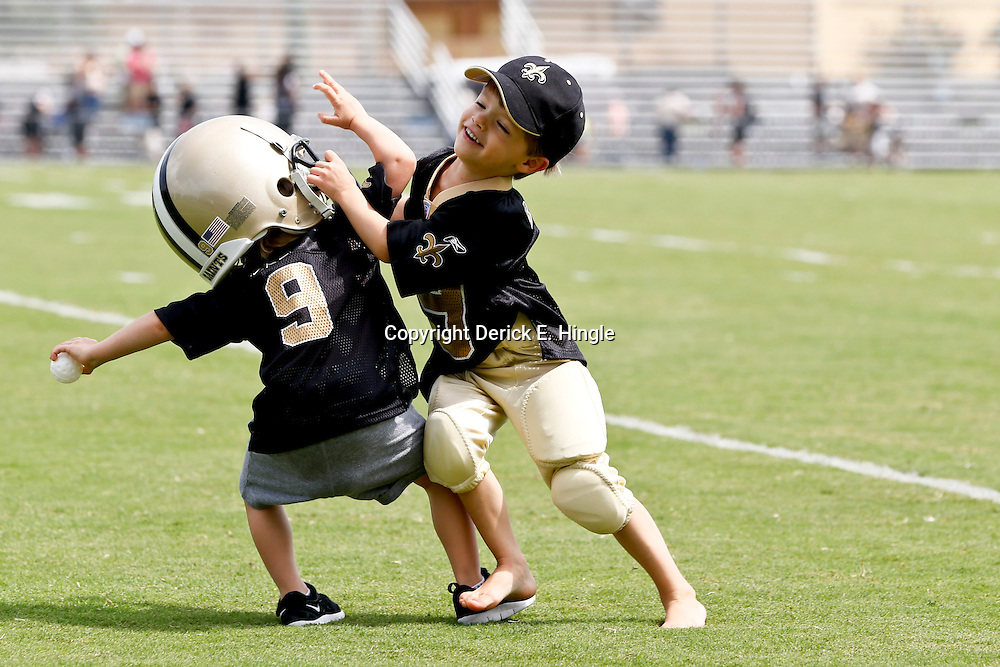 Aug 3, 2013; Metairie, LA, USA; New Orleans Saints quarterback Drew Brees (not pictured) sons Baylen Brees (right) tackles his younger brother Bowen Brees as the kids played on the field following a scrimmage at the team training facility. Mandatory Credit: Derick E. Hingle-USA TODAY Sports