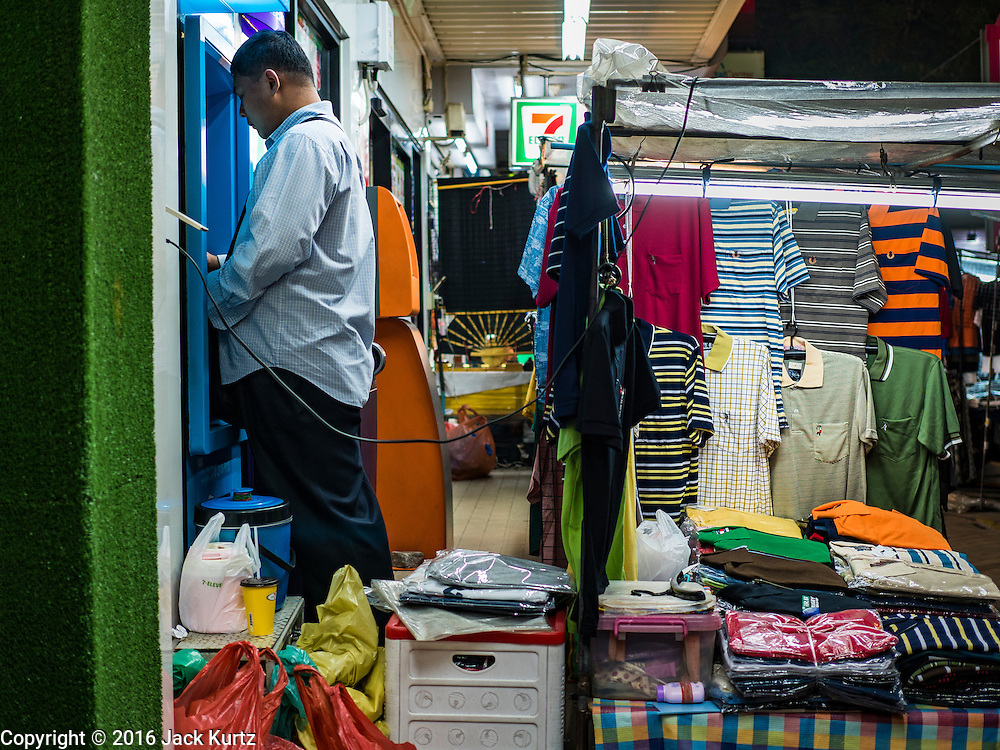 26 MAY 2016 - BANGKOK, THAILAND: A man uses an ATM wedged between a convenience store and a booth selling shirts in the Silom Road night market. The night market on Silom Road, close to Bangkok's famous Patpong tourist area, is being closed by the Bangkok municipal government. Vendors have been told they have to leave the sidewalk on Silom Road by the end of May, 2016. The market is the latest street market being shut down by city officials as a part of the government's plan to clean up Bangkok. The Silom Road night market sells mostly tourist oriented clothes, inexpensive Thai art, and bootleg movies on DVD.       PHOTO BY JACK KURTZ