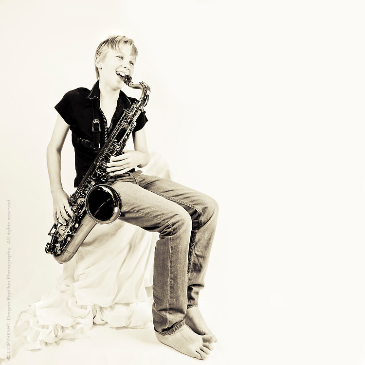 studio portrait in soft sepia tones and square format playing tenor saxophone
