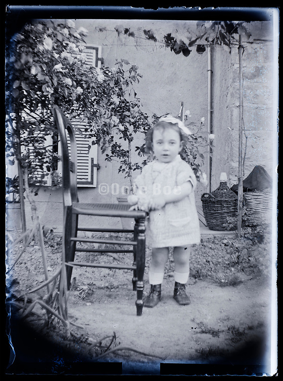 toddler girl holding on a chair in garden setting France 1923