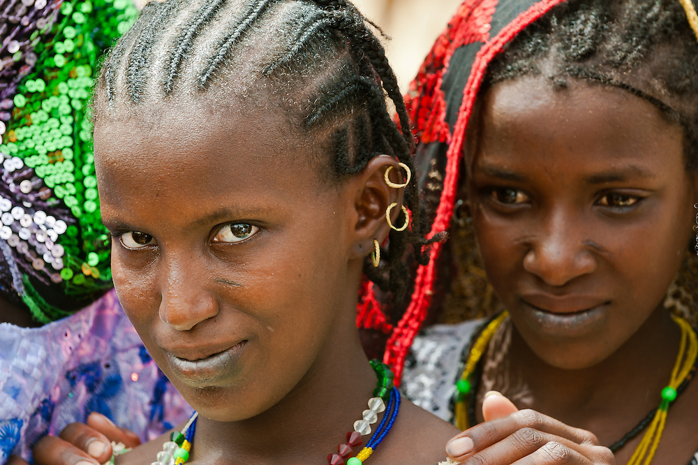 Portrait of two Fulani girls dressed in colourful traditional clothes in a local market in northern Burkina Faso. The Fulani or Peul are nomadic herdsmen of the Sahel region of West Africa. The darker lower lip from indigo staining, facial tattoos and silver jewellery are traditional markings of Fulani women.