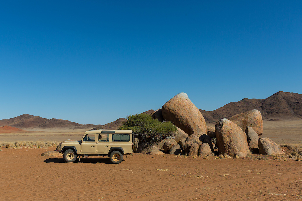 rock outcrop with safari vehicle, Namibrand nature reserve, Sossusvlei Area, Namibia
