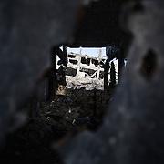 """Shejaya, quartiere a nord della striscia di Gaza. Una delle zone piu colpite dall'attacco israeliano """"Margine protettivo"""". Il quartiere è stato raso al suolo. La popolazione, a distanza di sei mesi dalla fine della guerra, vive tra le macerie della propria casa, al freddo, senza luce, gas e acqua. Nella foto all'interno di una casa, tra le lamiere si intravede una casa distrutta.  Dalla fine della guerra le macerie non sono state rimosse."""
