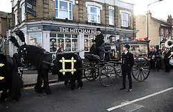 **NOTE: People in police uniform are not real policemen** © Licensed to London News Pictures. 09/12/2015. London, UK. A man dressed as a policeman stands next to The carriage carrying the coffin. The funeral of former brothel keeper Cynthia Payne takes place at the South London Crematorium.  In 1980 Cynthia Payne was sentenced to 18 months for running a brothel at her house on Ambleside Avenue in Streatham. It was alleged, at the time, that judges and Members of Parliament were visitors to her establishment. Photo credit: Peter Macdiarmid/LNP