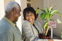 Middle-aged couple in front of new house, woman with potted plant