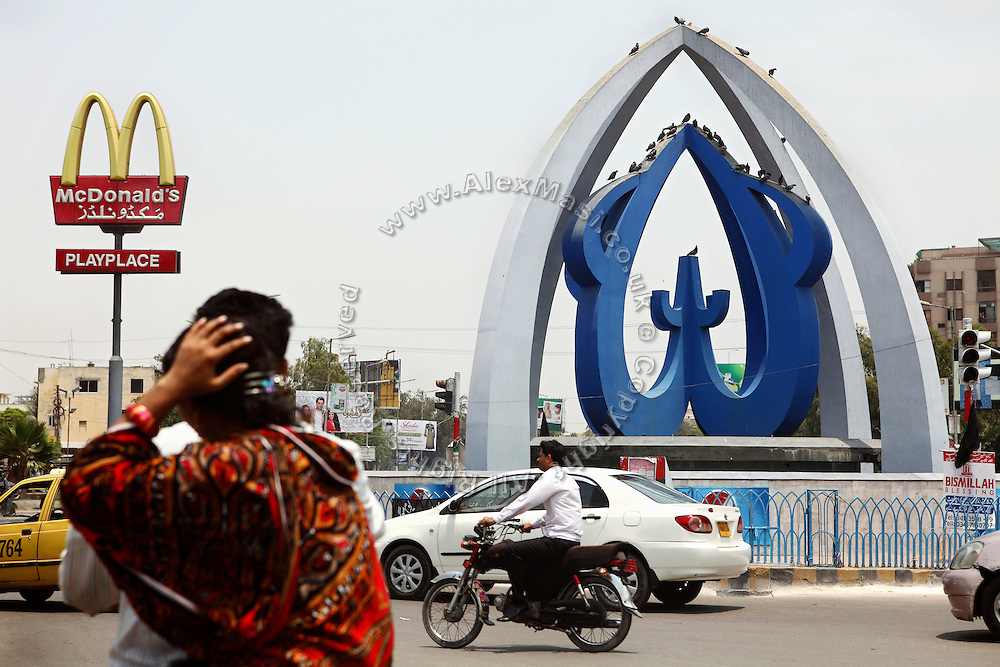 A symbol signifying 'Allah', (right) is seen at a roundabout in central Karachi near a McDonald's fast-food restaurant sign. (left)