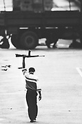A Muslim extremist walks toward waiting soldiers with his refile held high in surrender 1 August, 1990 in Port of Spain, Trinidad.  Extremists holding the Parliment building surrendered to the Trinidad army, releasing seventeen hostages.