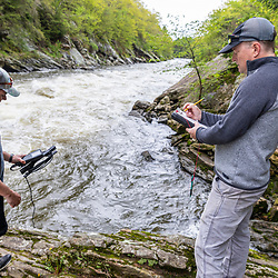 A scientist from the Gulf of Maine Research Institute takes water measurements while studying alewives during their spring spawning run on the Presumpscot River in Portland, Maine.
