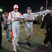 Racecar driver Dale Earnhardt Jr. is seen in his garage area signing autographs during the  56th Annual NASCAR Daytona 500 practice session at Daytona International Speedway on Wednesday, February 19, 2014 in Daytona Beach, Florida.  (AP Photo/Alex Menendez)