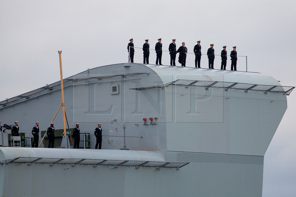 © Licensed to London News Pictures. 16/11/2019. Portsmouth, UK.  Crew lined up on the bow ramp of HMS Prince of Wales, the Royal Navy's second Queen Elizabeth-class aircraft carrier, as she sails into Portsmouth Naval Base for the first time this afternoon, 16th November 2019. The £3.1 billion warship has been undergoing eight weeks of sea trials in the Moray Firth. Photo credit: Rob Arnold/LNP