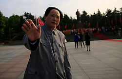 A Chairman Mao look-alike actor gestures to stop a photographer from taking his photo on the Mao Zedong Bronze Statue Square in Shaoshan, Hunan Province in central China, 27 April 2016. Shaoshan is the hometown of former Communist leader Mao Zedong, popularly known as Chairman Mao. Thousands of visitors descend on this small Chinese town burrowed in the hills of Central China's Hunan province to pay homage to the great helmsman everyday. It is one of the core sites of the 'Red Tourism' industry, where communist party cadres and ordinary Chinese tourists alike seek to relive the experiences and rekindle the spirit of the revolutionaries.