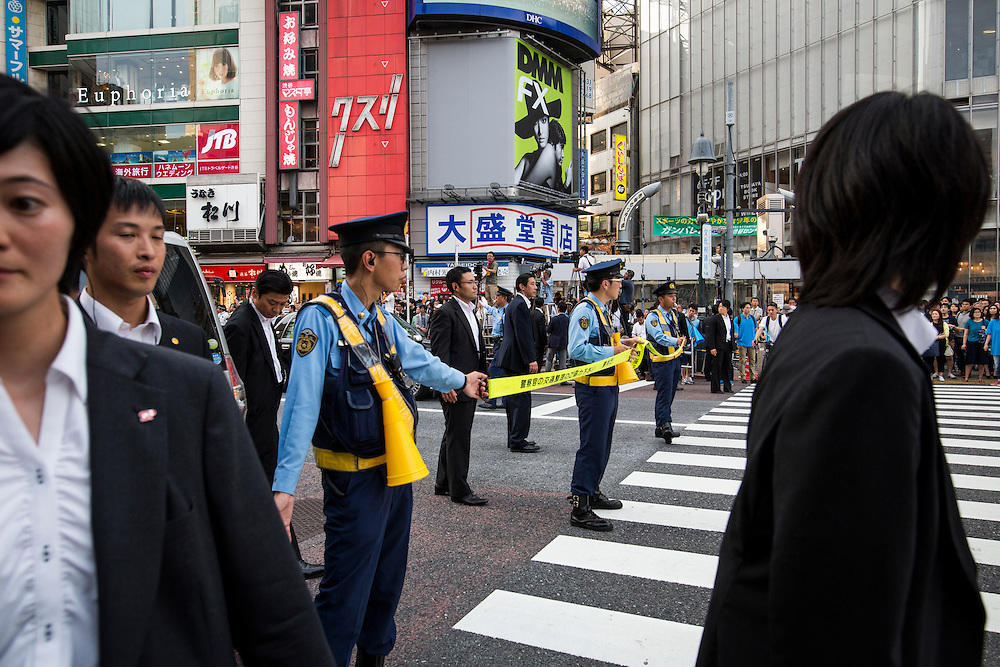 TOKYO, JAPAN - JULY 03 : Japanese policemen guard the pedestrians during the campaign rally of Prime Minister Shinzo Abe, president of the ruling Liberal Democratic Party (LDP), during the Upper House election campaign in Shibuya crossing, Tokyo prefecture, Japan, on July 3, 2016. (Photo by Richard Atrero de Guzman/ANADOLU AGENCY)