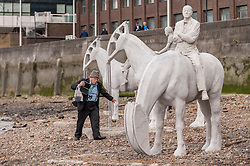 "© Licensed to London News Pictures. 02/09/2015 London, UK. A man walks amongst the art installation entitled ""The Rising Tide"" (comprising four horse-riders on horses with petroleum pumps for heads) by the underwater eco-sculptor Jason deCaires Taylor, which stands on the foreshore of the River Thames in Vauxhall and is revealed with each low tide.  The installation aims to question man's reliance on fossil fuels and is part of this year's Totally Thames festival. Photo credit : Stephen Chung/LNP"