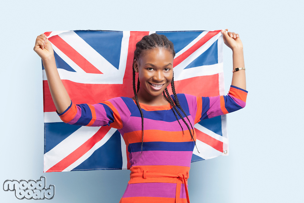 Portrait of a young woman with braided hair holding British flag over light blue background