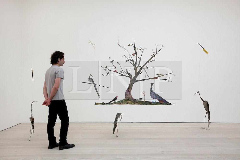 © Licensed to London News Pictures. 17/06/2013. London, UK. A Saatchi Gallery employee views 'Nature Scene' (background) (2011) and 'Congregation' (2010) by American artist Tom Thayer at the press view for a new exhibition taking place at the West London based gallery. The exhibition, which runs from the 18th of June to the 29th of September 2013 at the Saatchi Gallery, is entitled 'Paper' and aims to challenge the viewers perceived ideas and expectations of the material in a world where its use is becoming rare thanks to emails and the internet  Photo credit: Matt Cetti-Roberts/LNP