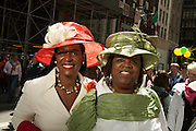 Two smiling women in elaborate straw hats in complementary red and green.