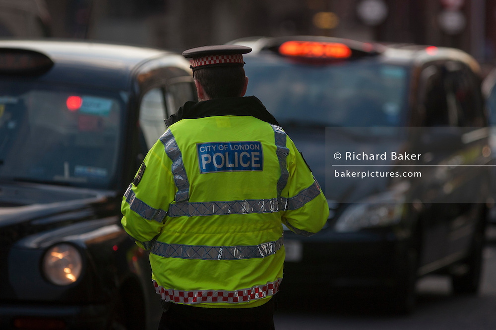 A City of London police officer notes the license numbers of black London cabs while they protest about their being banned from City road junctions, on 18th January 2017, in Parliament Square, London England.