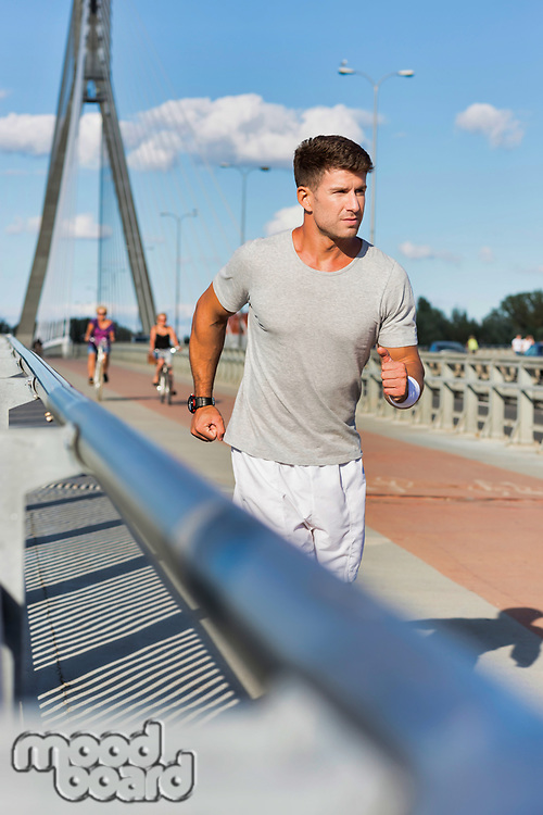Portrait of young attractive man running in the middle of the city