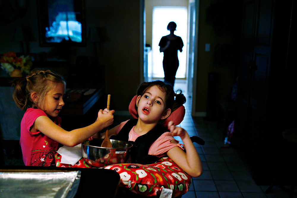 MELISSA LYTTLE   |   Times<br /> SP_351237_LYTT_TWINS_4 (March 8, 2012, Clearwater, Fla.) While making granola with their mom, Hailey Scheinman, 7, left, helps her twin sister Olivia stir the oats. Taking her hand and leading the way, Hailey always tries to include Olivia in activities that she can do with ease.  [MELISSA LYTTLE, Times]