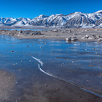 On a very cold, crisp morning, ice covers the north section of Mono Lake, with the snow covered Eastern Sierra mountains in the background.