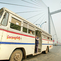 Jan 13, 2013 -  Kolkata, India. A bus crosses the Howrah Bridge as more than 75% of the vehicles in Kolkata have managed to skip out on the government mandated anti-pollution control testing. The pollution measurements are 20% to 50% higher than safe limits at many parts of the city.<br /> <br /> Story Summary: It is said that the battle over global warming is to be won or lost in Asia. With growing populations and new economic boom in the global markets across Asia countries like India, Nepal and Cambodia have to grapple with the success and the environmental disaster that comes with ramped up production in unchecked or unregulated industries to compete in todays marketplace. The catastrophic air pollution makes for new problems to be dealt with such as a future health crisis, quality of life issues and the tarnished image of reduced visibility to world heritage sites for tourism.
