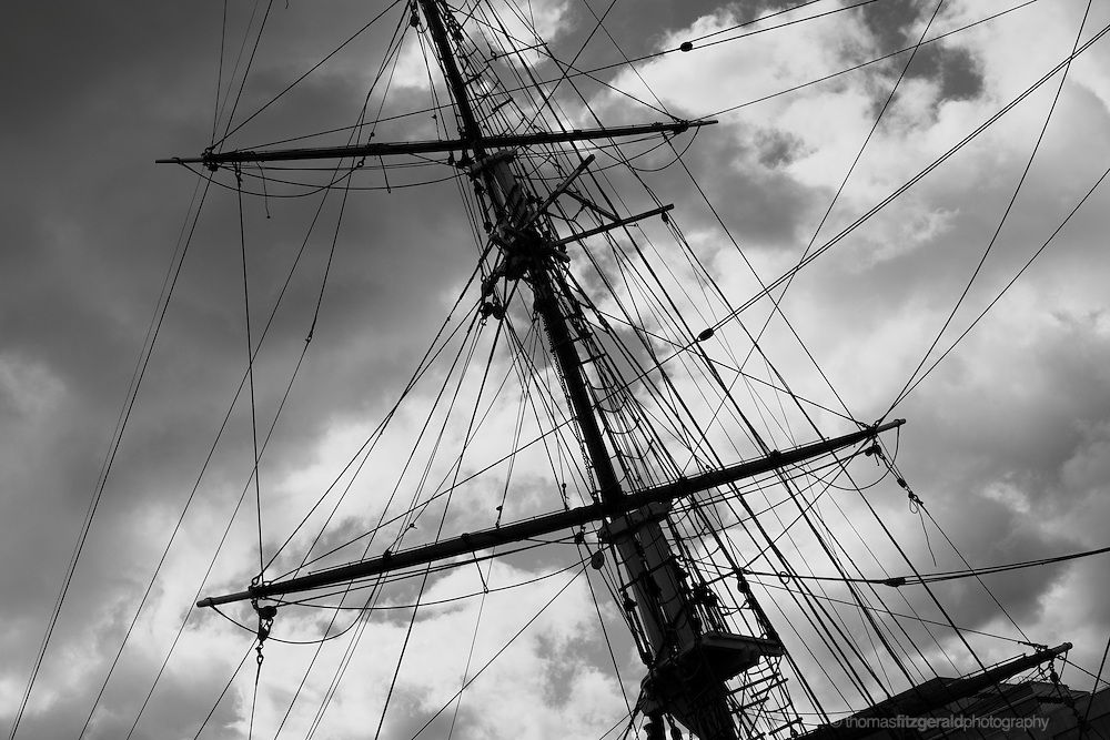 Silhouette of tall ship rigging against a cloudy sky. black and White