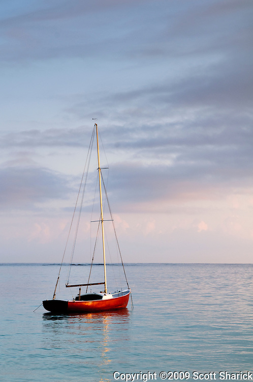 A peaceful sunrise scene of a red sailboat on Kailua Bay on the island of Oahu, Hawaii.