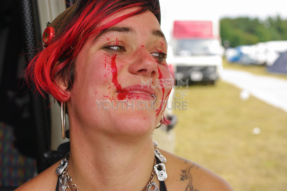 A portrait of woman with red hair and faceprint wearing a necklace made of ring pulls, Boomtown, Matterley Estate, Alresford Road, near Winchester, Hampshire, UK, August, 2010