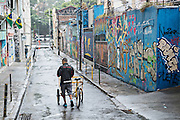 A bicycle delivery rider makes his way down a graffiti covered street in the Lapa neighborhood of Rio de Janeiro, Brazil.