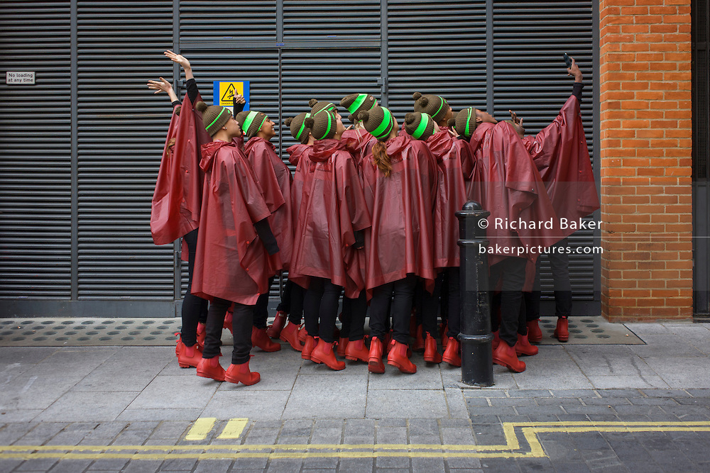 Dancers take a selfie before performing for the UK company Hunter perform a choreographed dance routine to officially launch the brand's flagship new store in London's Regent Street. Twenty Eight dancers stopped shoppers with their production of 'Singin' in the Rain.'