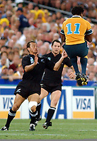 Photo. Steve Holland.Australia v New Zealand, Semi-final at the Telstra Stadium, Sydney. RWC 2003.<br />15/11/2003.<br />Australia's Lote Tuqiri, right jumps for the ball with Nz's Carlos Spencer, right