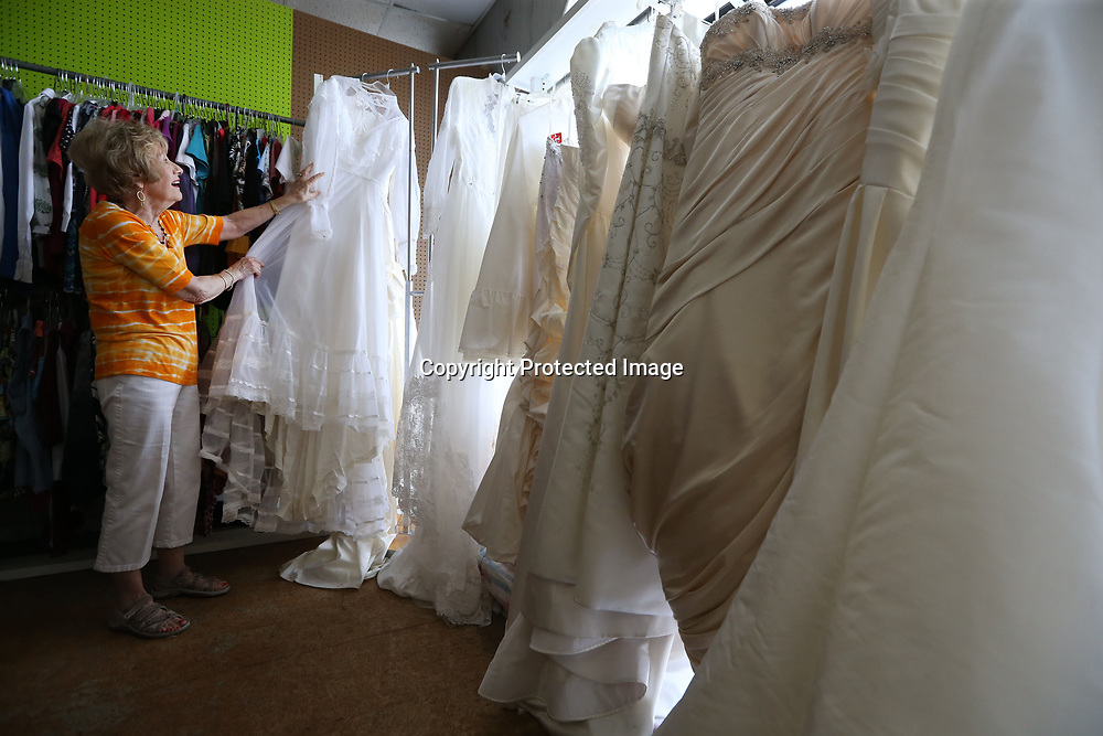 Cherie Harris, a volunteer at the Sanctuary Village Shoppe, sorts through a sales rack of wedding dresses on Thursday afternoon in Tupelo. The thrift store that benefits the Sanctuary Hospice House gets a surprising number of wedding dresses which they sell for $50.00.