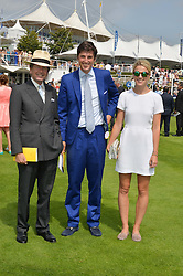Left to right, SIR JOHN WARREN, his son JAKE WARREN and his wife ZOE at the 2014 Glorious Goodwood Racing Festival at Goodwood racecourse, West Sussex on 31st July 2014.
