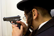 An Orthodox Jewish teenage boy with his finger on the trigger while playing with a replica hand gun.
