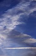 Trainées d'un avion dans un ciel bleu nuageux. Kondensstreifen eines Flugzeugs im wolkenverhangenen Himmel. © Romano P. Riedo