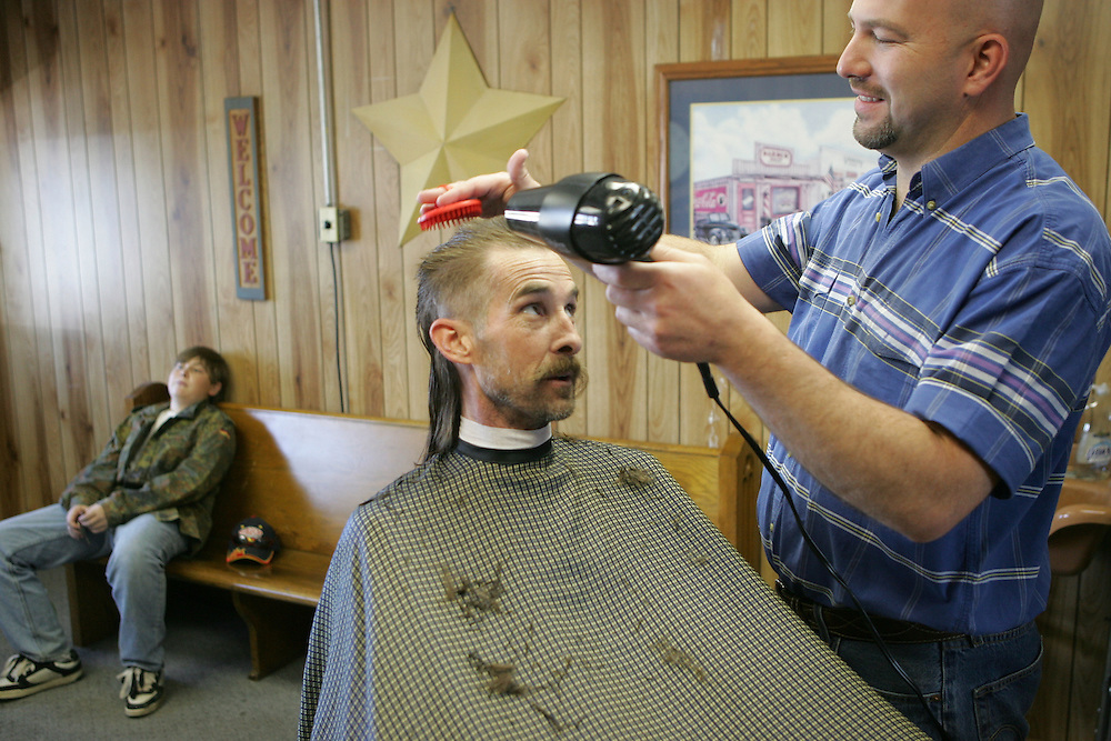 photography / Troy Boman.Glen Gordon gets his hair cut by Grantsville Barber Paul Cook. Gordon's son David waits in the background. Glen Gordon lives in Salina, UT some 150 miles southeast of Grantsville. Gordon has had his hair cut by Paul Cook for the last seven years.