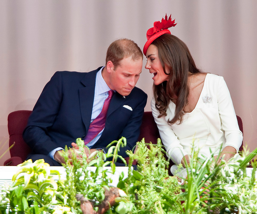 Catherine the Duchess of Cambridge speaks to her husband Prince William as the couple took part in Canada Day celebrations on Parliament Hill in Ottawa, Canada, July 1, 2011. The Duke and Duchess are on a nine day tour of Canada, their first official foreign trip as husband and wife.<br /> AFP PHOTO/GEOFF ROBINS