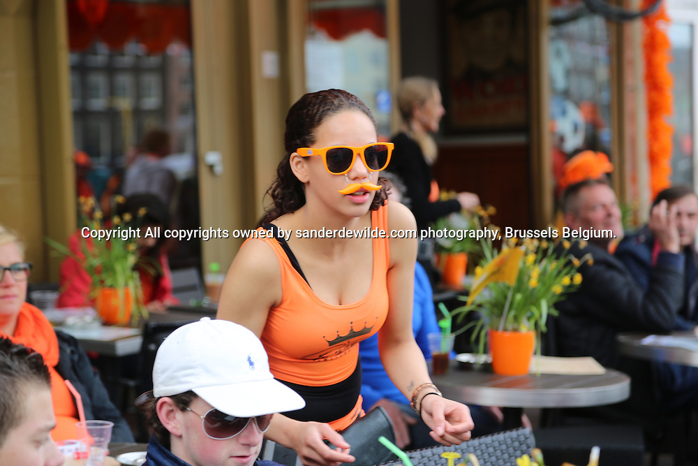 30th April 2013 Amsterdam, Netherlands. Queen Beatrix' abdication day, where her son Prince Willem-Alexander became King of the Netherlands. A sexy girl with orange glassses, moustache and shirt serves clients at a terrace in Amsterdam