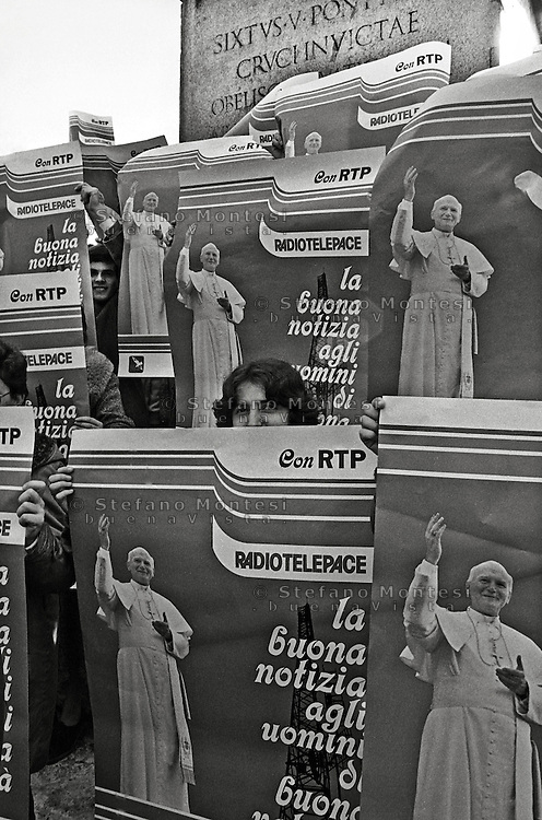 Roma, 1987 Piazza San Pietro.  Un gruppo di giovani  con i manifesti  con il ritratto di Papa Giovanni Paolo II, rivolto verso la finestra papale in attesa dell'angelus. .Rome, 1987 St. Peter's Square. A group of young people with the posters with the portrait of Pope John Paul II, facing the window waiting  the papal Angelus.