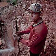 Brasile, Amazzonia, garimpo de Juma. Le miniere a cielo aperto del garimpo de Juma, dove la vita dei minatori scorre tra pericolo per un lavoro al limite e deforestazione incontrollata. Aspettando di trovare l'oro che cambi la loro vita. In questa foto un minatore si prende un momento di pausa dalla calura insopportabile mentre lavora pericolosamente sul bordo di una montagna. Brazil, Amazonia, garimpo de Juma. The open pit mines of garimpo de Juma, where the miners work flows between danger and uncontrolled deforestation. Waiting to find the gold that changes their lives. In this picture, a miner takes a break from the unbearable heat while working dangerously on the edge of a mountain.
