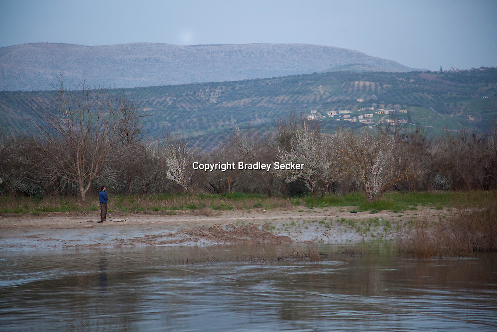 A man praying on the bank of the Orontes river. The river, known in Arabic as the Assie marks the international boundry between Turkey and Syria. February 27th 2013, Hacipasa, Turkey.