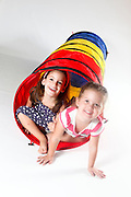 Indoor playground two girls emerge from a tunnel On white Background