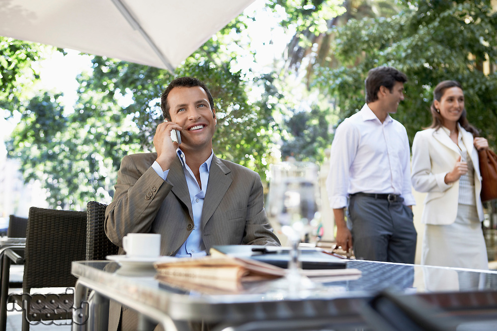 Businessman using mobile phone at outdoor cafe